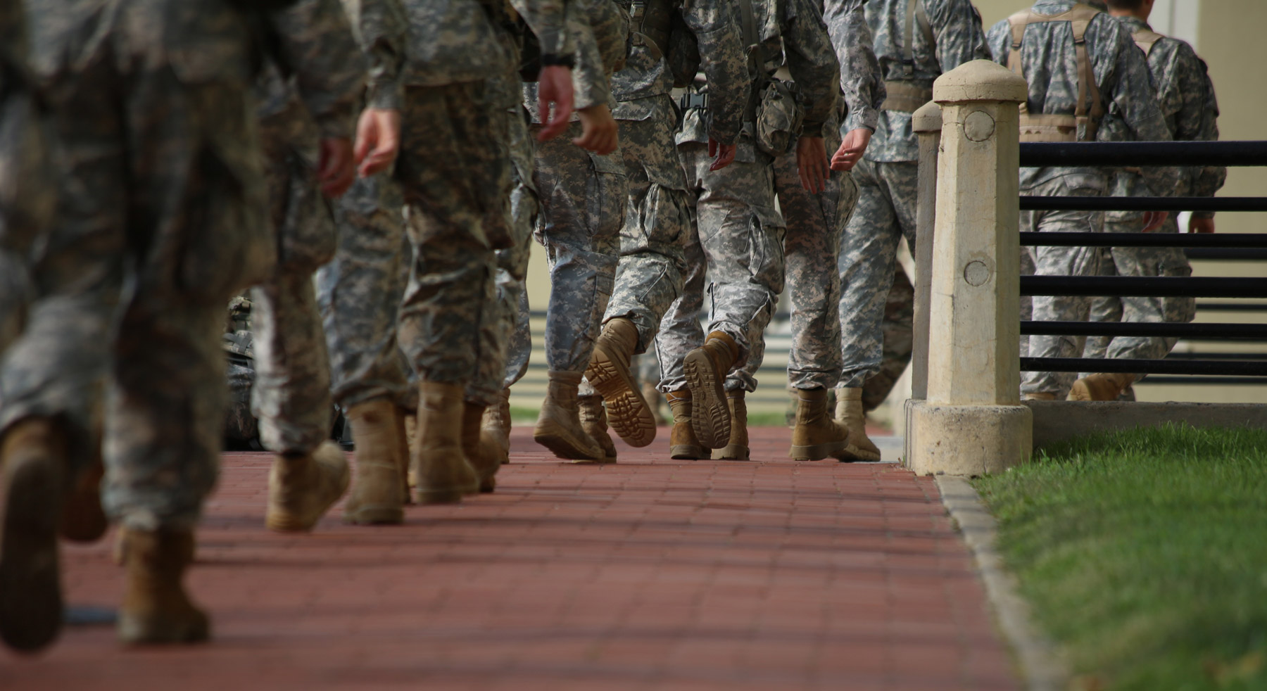 group of soldiers marching on brick path